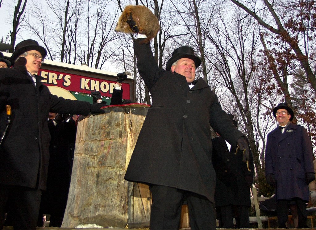 . Punxsutawney Phil, the weather prognosticating groundhog from Gobblers Knob in Punxsutawney, Pa., is held high by handler Bill Deeley, center,  after seeing his shadow at 7:27 am Monday, Feb. 2, 2004, and predicting six more weeks of winter. (AP Photo/Gene J. Puskar)