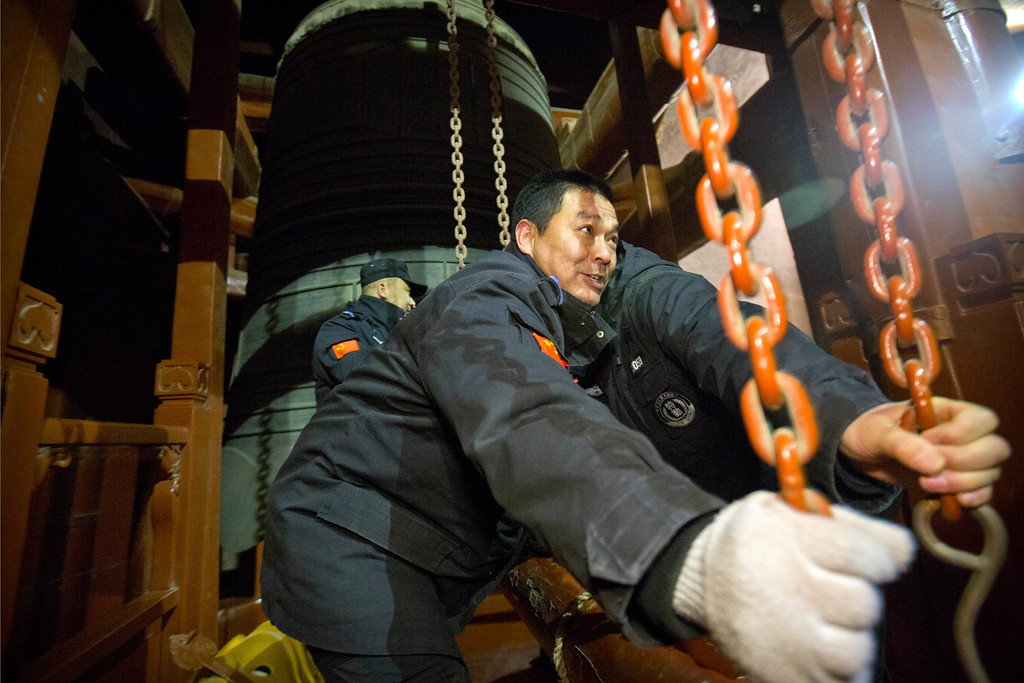 . Security officials ring the bell at midnight to mark the arrival of the Lunar New Year at the Bell Tower in Beijing, Friday, Feb. 16, 2018. (AP Photo/Mark Schiefelbein)