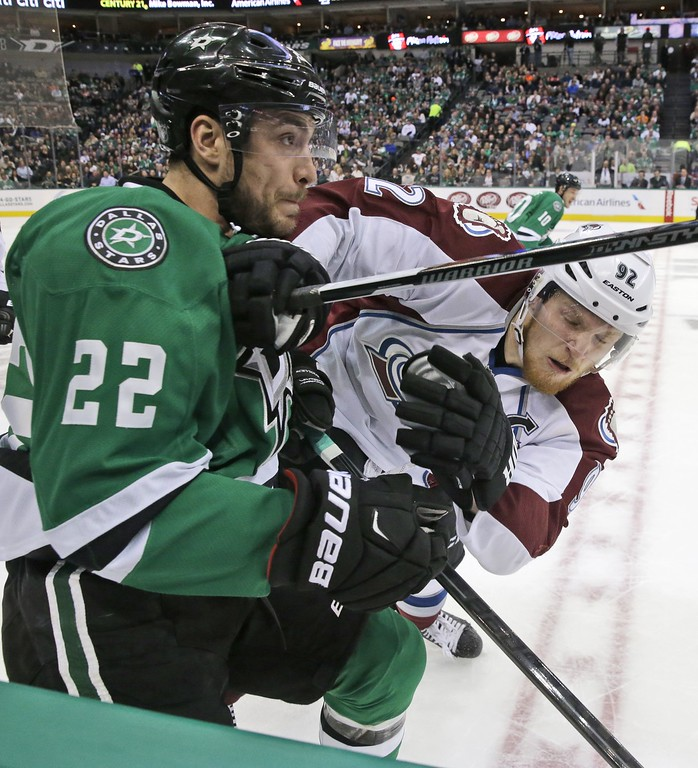 . Colorado Avalanche left wing Gabriel Landeskog (92) and Dallas Stars center Colton Sceviour (22) crash into the boards during the first period of an NHL hockey game Tuesday, Feb. 3, 2015, in Dallas. (AP Photo/LM Otero)