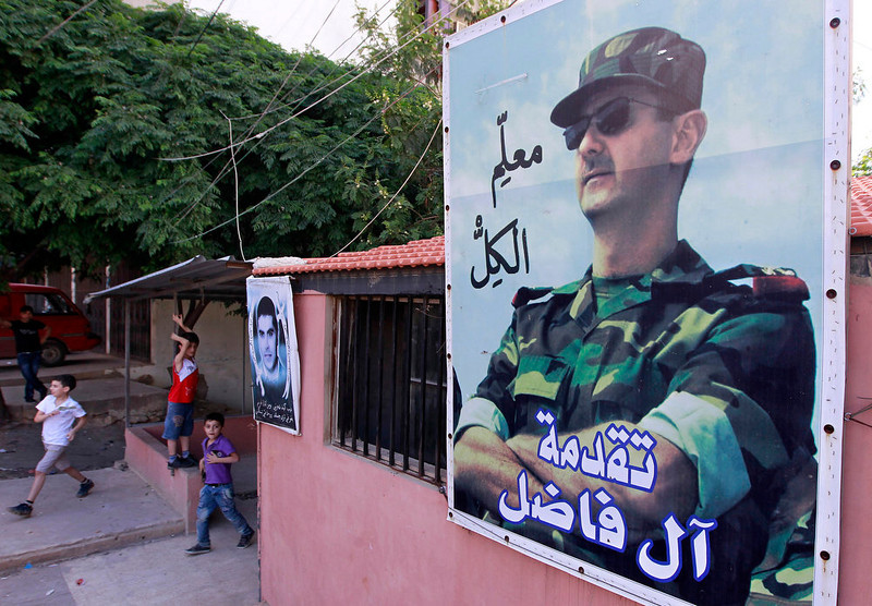 ". Lebanese boys play under a large poster, right, of Syrian President Bashar Assad with Arabic writing that reads, ""everybody\'s teacher,\"" in the predominantly Alawite neighborhood of Jabal Mohsen in the northern port city of Tripoli, Lebanon on Tuesday, April 30, 2013.  Lebanese members of the Syrian leader\'s Alawite sect fear their tiny community will be a casualty of the civil war raging in the neighboring country. Already, Sunni extremists have stoned a school bus, vandalized stores and beaten or stabbed a number of men in a wave of attacks against Lebanese Alawites, raising fears of more violence should Assad be removed from power.  (AP Photo/Bilal Hussein)"