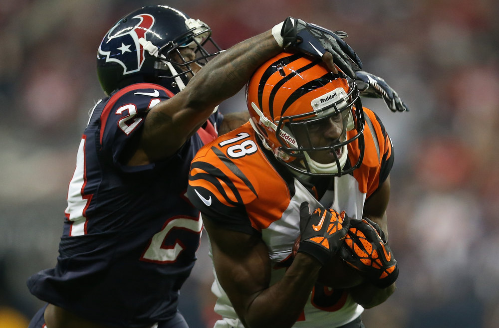 Description of . A.J. Green #18 of the Cincinnati Bengals makes a pass reception against Johnathan Joseph #24 of the Houston Texans during the AFC Wild Card Playoff Game at Reliant Stadium on January 5, 2013 in Houston, Texas.  (Photo by Ronald Martinez/Getty Images)