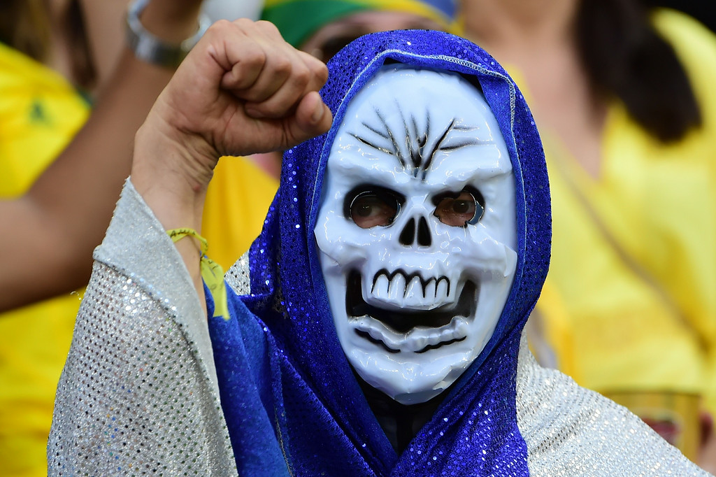 . A masked fan cheers during the round of 16 football match between Costa Rica and Greece at Pernambuco Arena in Recife during the 2014 FIFA World Cup on June 29, 2014.   RONALDO SCHEMIDT/AFP/Getty Images