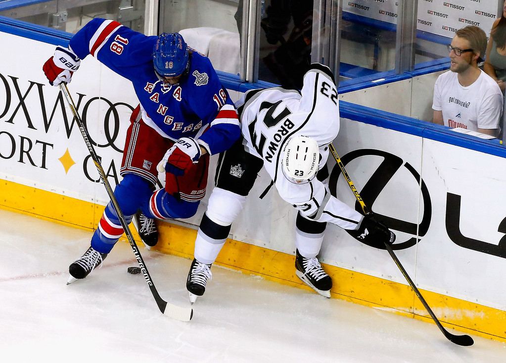 . Marc Staal #18 of the New York Rangers and Dustin Brown #23 of the Los Angeles Kings battle for the puck during Game Three of the 2014 NHL Stanley Cup Final at Madison Square Garden on June 9, 2014 in New York, New York.  (Photo by Jim McIsaac/Getty Images)