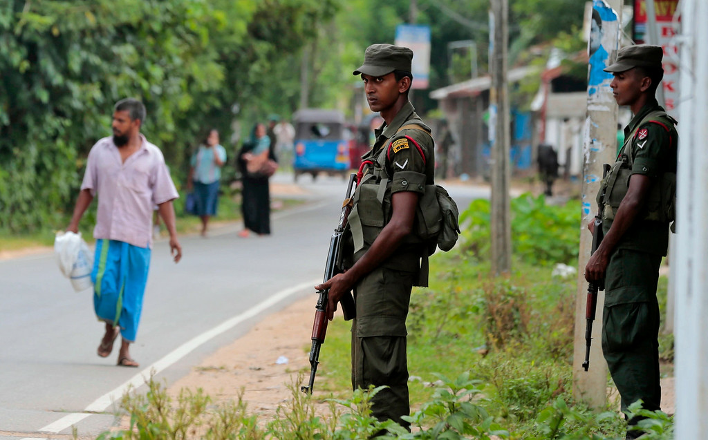 . In this Friday, June 27, 2014 photo, Sri Lankan army soldiers stand guard at a Muslim neighborhood in Darga Town in Aluthgama about 50 kilometers (31 miles) south of Colombo, Sri Lanka. The onslaught by the Bodu Bala Sena (BBS), a hardline Buddhist group, killed two Muslims in the worst religious violence Sri Lanka has seen in decades. (AP Photo/Eranga Jayawardena)