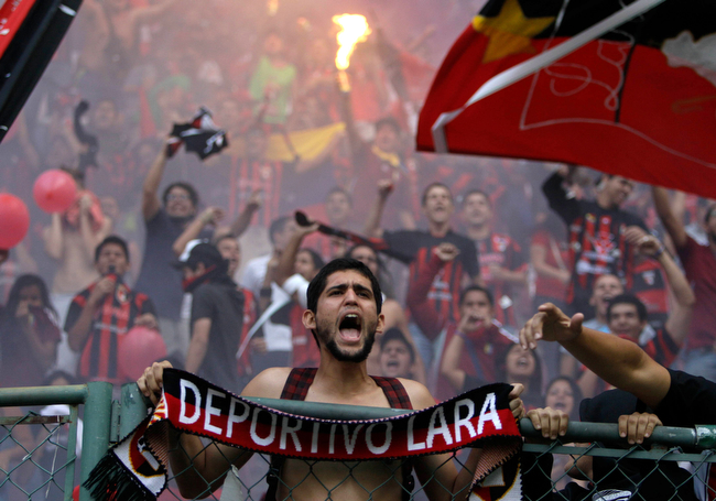 Description of . A fan of Venezuela's Deportivo Lara cheers his team during a Copa Libertadores soccer match against Argentina's Newell's in Barquisimeto, Venezuela, Thursday, Feb. 21, 2013. (AP Photo/Fernando Llano)
