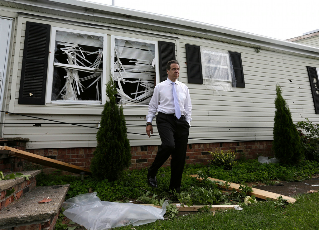 . New York Gov. Andrew Cuomo walks near a house that was damaged from Tuesday\'s storm, on Wednesday, July 9, 2014, in Smithfield, N.Y. (AP Photo/Mike Groll)