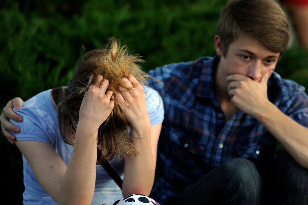 . Nathan Mendonca, 18, right, comforts, his girlfriend Melissa Clark, 18 at the memorial service for shooting victims at the parking lot of Kaiser Permanente in Aurora, Colo. on Friday, July 20, 2012. Hyoung Chang, The Denver Post