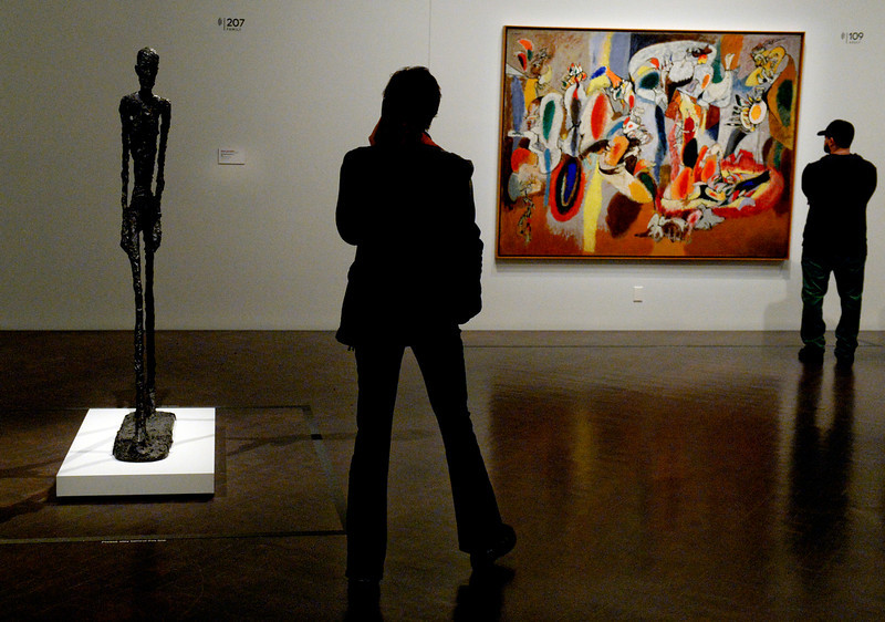 """. The bronze sculpture of Alberto Giacometti, left, \""""Man Walking (Version I)\"""" and Arshile Gorky\'s painting, \""""The Liver is the Cock\'s Comb\"""" at  the Denver Art Museum\'s new exhibition, \""""Modern Masters: 20th Century Icons from the Albright-Knox Art Gallery\""""  on Wednesday, March 5,  2014. The exhibit brings to the space some of the art world\'s most recognizable names. Picasso, Van Gogh, Warhol,    (Denver Post Photo by Cyrus McCrimmon)"""