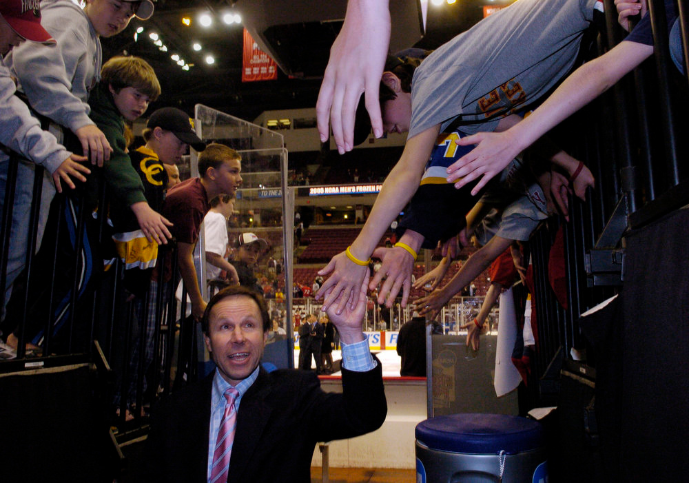 . Denver University Pioneer head coach, George Gwozdecky, celebrates with the fans walking to the locker room after defeating the North Dakota Sioux 4-1 for the 2005 NCAA Division 1 Hockey Championship game at the Schottenstein Center in Columbus, Ohio Saturday evening. THE DENVER POST/ ANDY CROSS