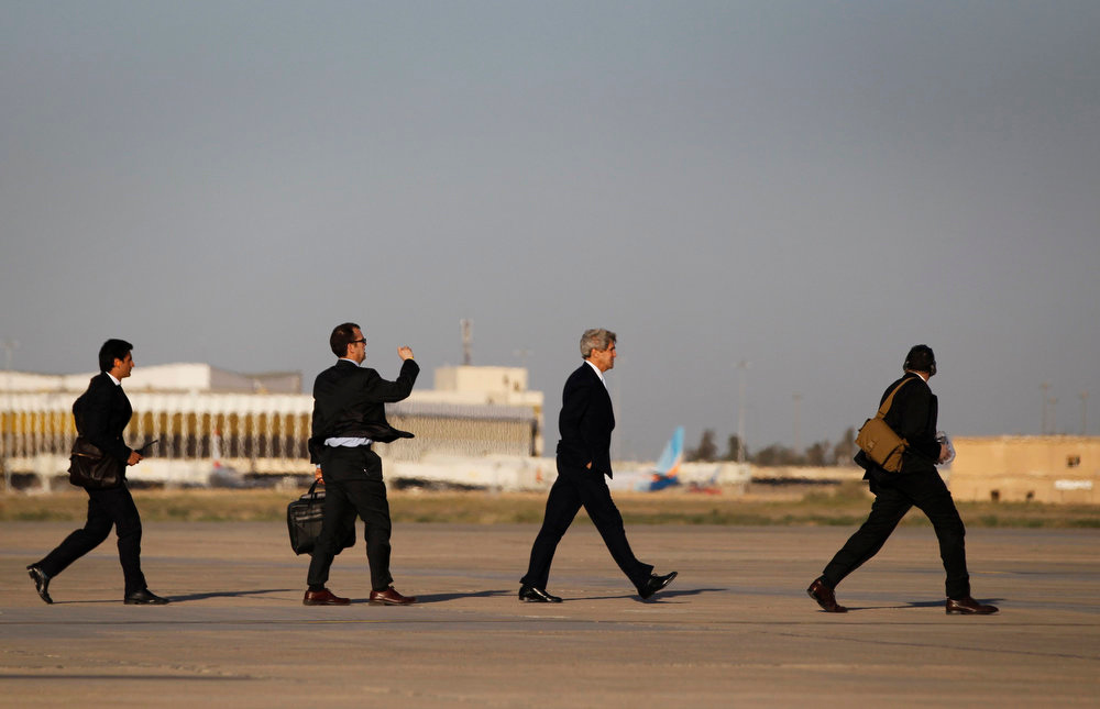 . U.S. Secretary of State John Kerry (2nd R) walks across the tarmac of Baghdad International Airport with traveling staff as he prepares to board an aircraft out of the Iraqi capital March 24, 2013. Kerry made an unannounced visit to Iraq on Sunday and said he told Prime Minister Nuri al-Maliki of his concern about Iranian flights over Iraq carrying arms to Syria.     REUTERS/Jason Reed