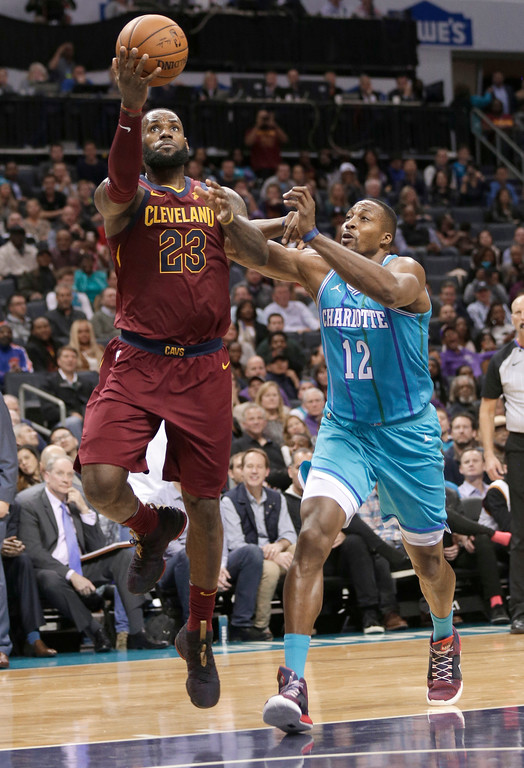 . Cleveland Cavaliers\' LeBron James (23) drives past Charlotte Hornets\' Dwight Howard (12) during the second half of an NBA basketball game in Charlotte, N.C., Wednesday, Nov. 15, 2017. (AP Photo/Chuck Burton)
