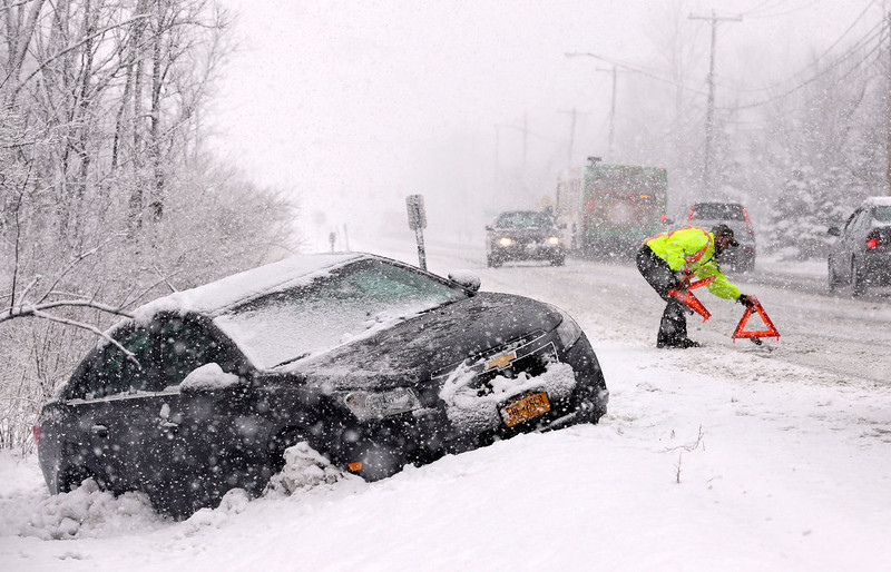 . Tow truck operator Shawn Juhre sets up road safety reflectors before towing a car out of a ditch during a winter snow storm in Buffalo, N.Y., Friday, Feb. 8, 2013. Snow began falling across the Northeast on Friday, ushering in what was predicted to be a huge, possibly historic blizzard and sending residents scurrying to stock up on food and gas up their cars. The storm could dump 1 to 3 feet of snow from New York City to Boston and beyond. (AP Photo/David Duprey)