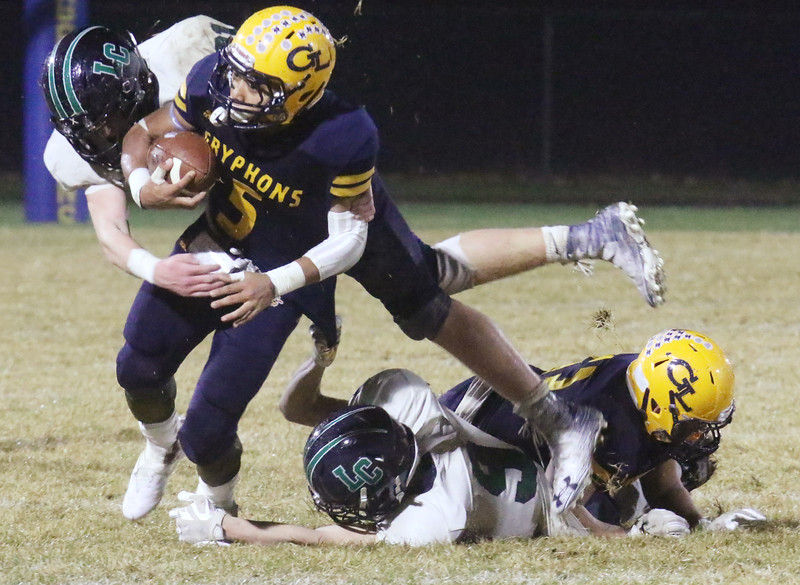 Greater Lowell Tech vs Lowell Catholic football.  Greater Lowell's Benji Hach (5), shakes off tackle by Lowell Catholic's Rowan Ruggiero (21). At rear are Greater Lowell's Monetry Vilavong (53), and Lowell Catholic's Aidan Maston (9). (SUN/Julia Malakie)