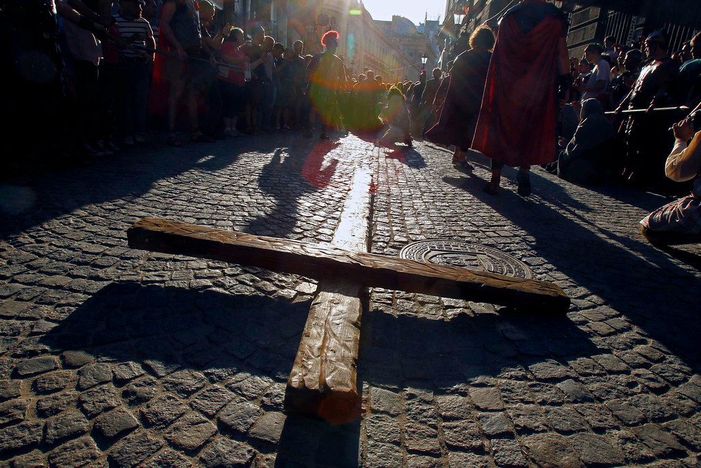 """. The cross is seen on the ground as actors take part in a re-enactment of the \""""Via Crucis\"""" (Way of the Cross), which commemorates the crucifixion of Jesus Christ, during the Orthodox Church\'s Good Friday celebrations in Bucharest May 3, 2013. Romania\'s Orthodox majority celebrates Easter on May 5.  REUTERS/Bogdan Cristel"""
