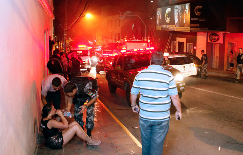 . Police agents give water to a woman after a fire at a nightclub in Santa Maria, 550 Km from Porto Alegre, southern Brazil on January 27, 2012. More than 150 people died early Sunday when a fire tore through a nightclub in the southern Brazilian city of Santa Maria during a boisterous student party, police said. Brazilian President Dilma Rousseff interrupted her visit to Chile. LAURO ALVES/AFP/Getty Images
