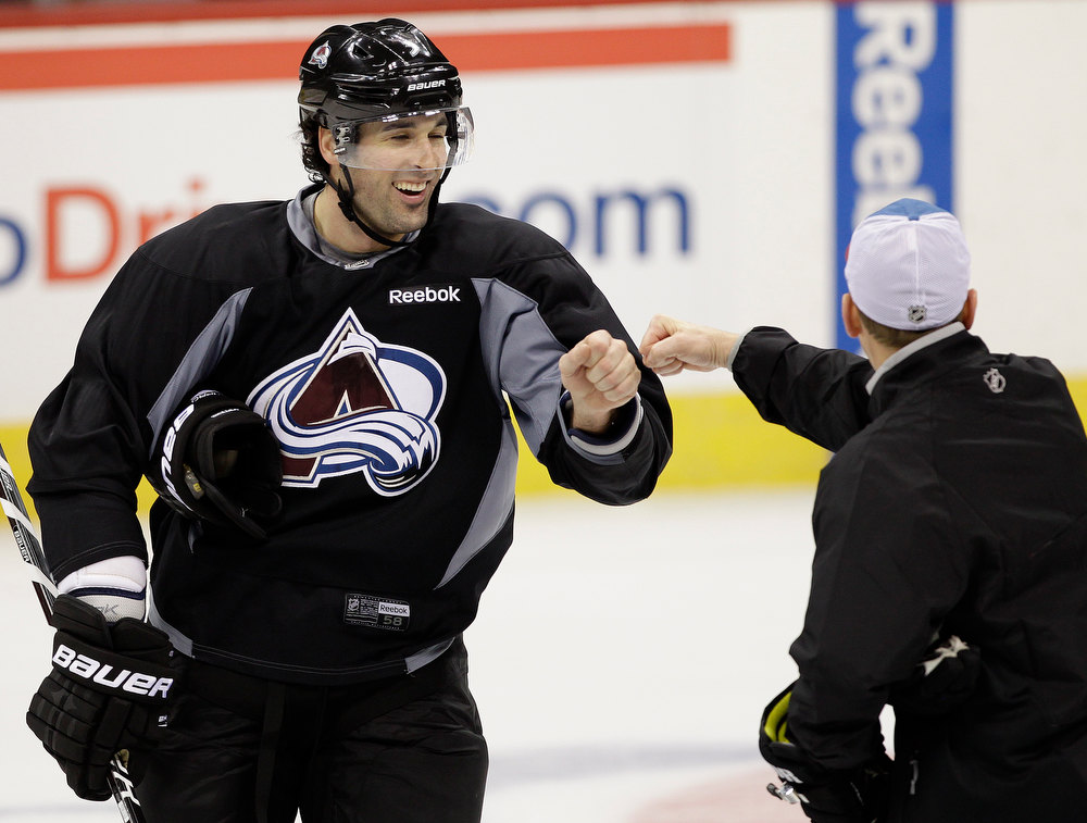 . Colorado Avalanche\'s Ryan O\'Byrne, left, gets a fist bump from a coach during NHL hockey practice, Thursday Jan. 17, 2013, in Denver, Colo. (AP Photo/Brennan Linsley)