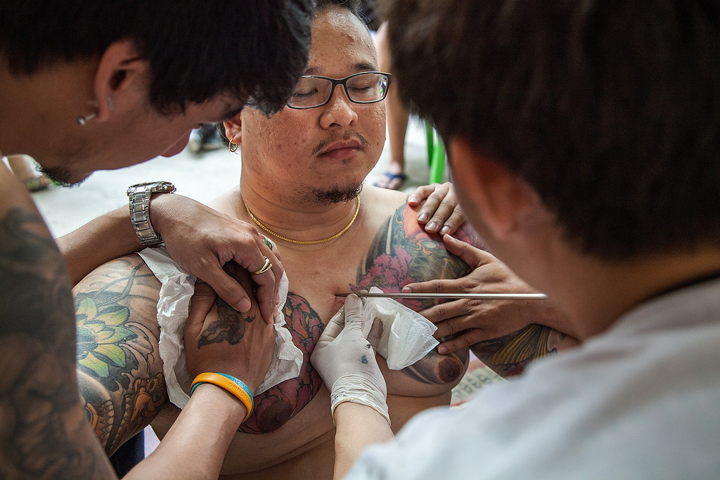 . A Thai tattoo master carves a tattoo on a devotee\'s chest with a long needle during the celebration of the annual Tattoo festival at Wat Bang Phra on March 15, 2014 in Nakhon Pathom, Thailand.  (Photo by Omar Havana/Getty Images)