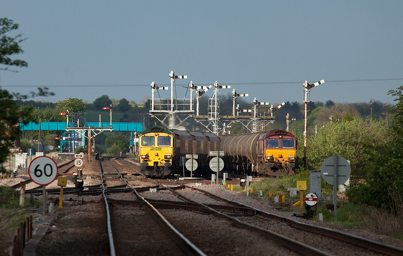 Freightliner 66606 on the 6R36 18:10 Immingham-Ferrybridge Powerstation loaded FHH coal hoppers and EWS 66207 with the 6V19 17:22 Immingham-Margam steel/fuel oil tanks depart simultaneously from Barnetby after being looped.