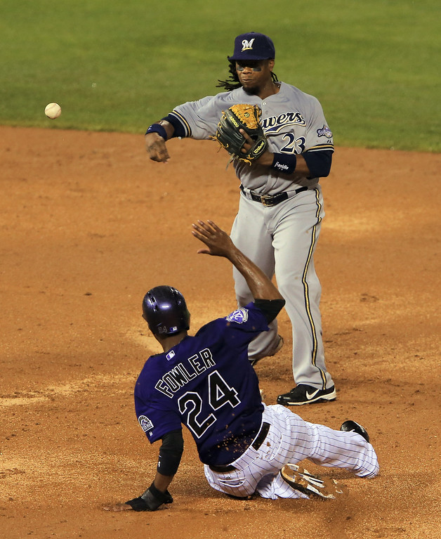 . DENVER, CO - JULY 27:  Second baseman Rickie Weeks #23 of the Milwaukee Brewers turns a double play on Dexter Fowler #24 of the Colorado Rockies to end the seventh inning at Coors Field on July 27, 2013 in Denver, Colorado.  (Photo by Doug Pensinger/Getty Images)