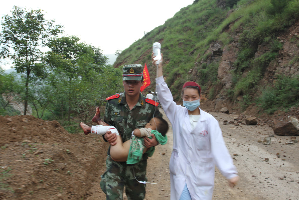 . Armed police and a nurse rescue the wounded after a 6.5-magnitude earthquake on August 3, 2014 in Zhaotong, Yunnan province of China. A 6.5-magnitude earthquake hit Zhaotong\'s Ludian county at a depth of 12 kilometers. The quake struck Longtoushan Township at 4:30 pm, Beijing time on Sunday, about 50 kilometers from the city center of Zhaotong. (Photo by ChinaFotoPress/Getty Images)