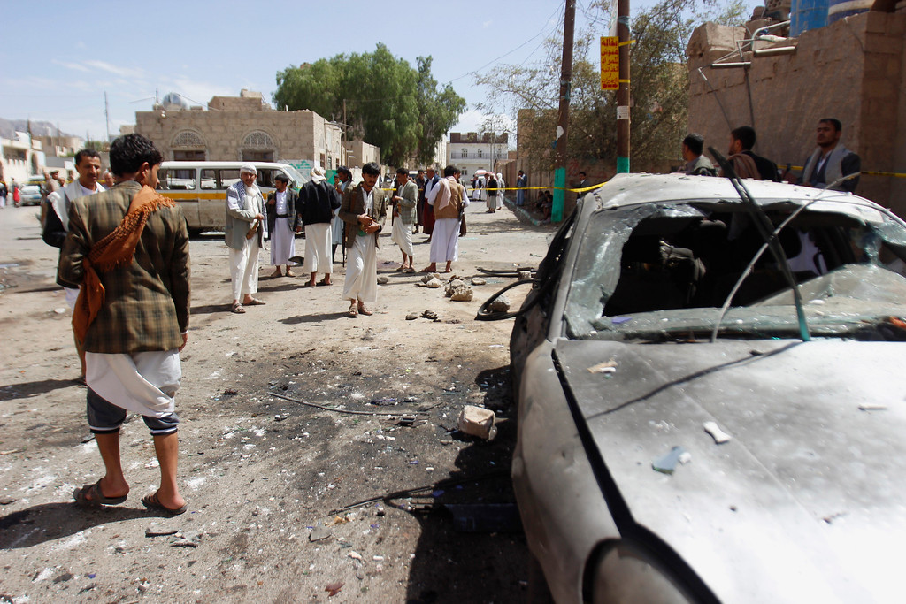 . Shiite rebels, known as Houthi, stand near a damaged car after a bomb attack in a mosque in Sanaa, Yemen, Friday, March 20, 2015. Triple suicide bombers hit a pair of mosques crowded with worshippers in the Yemeni capital, Sanaa, on Friday, causing heavy casualties, according to witnesses. The attackers targeted mosques frequented by Shiite rebels, who have controlled the capital since September. (AP Photo/Hani Mohammed)
