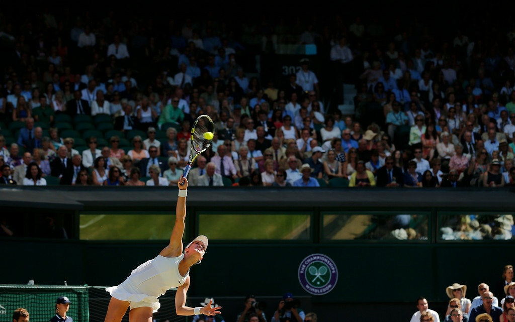 . Eugenie Bouchard of Canada serves to Simona Halep of Romania during their women\'s singles semifinal match at the All England Lawn Tennis Championships in Wimbledon, London, Thursday, July 3, 2014. (AP Photo/Ben Curtis)