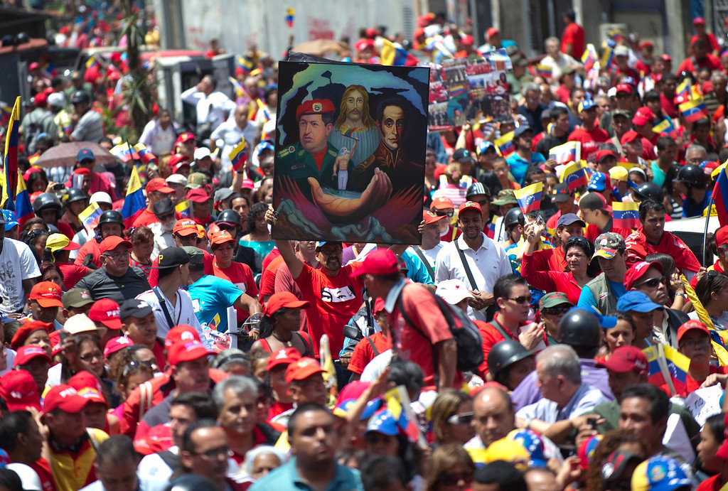 . Thousands of supporters of the late Venezuelan President Hugo Chavez accompany the funeral cortege on its way to the Military Academy, on March 6, 2013, in Caracas. The flag-draped coffin of Venezuelan leader Hugo Chavez was borne through throngs of weeping supporters on Wednesday as a nation bade farewell to the firebrand leftist who led them for 14 years. AFP PHOTO/Juan  BARRETO/AFP/Getty Images