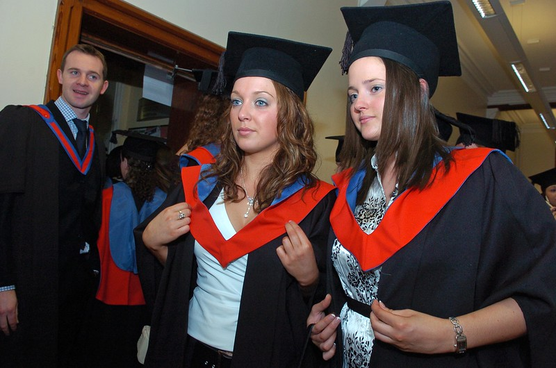 Provision 251006 Amanda Beere (Laois) and Charlene Barcoe (Carlow) adjust their gowns in the mirror before their graduation ceremony in WIT yesterday (Weds).  Both graduated with a BA in Legal Studies. PIC Bernie Keating/Provision