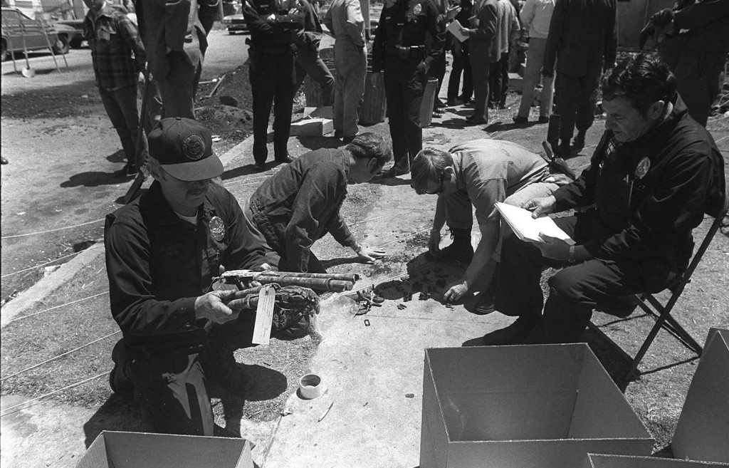 . Police officers catalogue more weapons found in the charred rubble of a Symbionese Liberation Army hideout in Los Angeles. Police said 18 guns have been recovered from the house. Officer at left holds what a spokesman said are two sawed-off shotguns. Officers at rear examine spent shells and ammunition. (undated) (AP Photo)