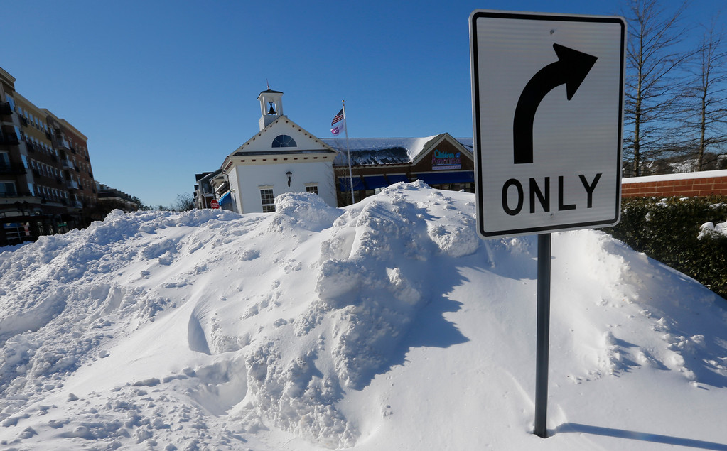 . A mound of snow nearly blocks an intersection at a shopping center as area residents dig out from a mammoth snowstorm in Richmond, Va., Sunday, Jan. 24, 2016.    (AP Photo/Steve Helber)