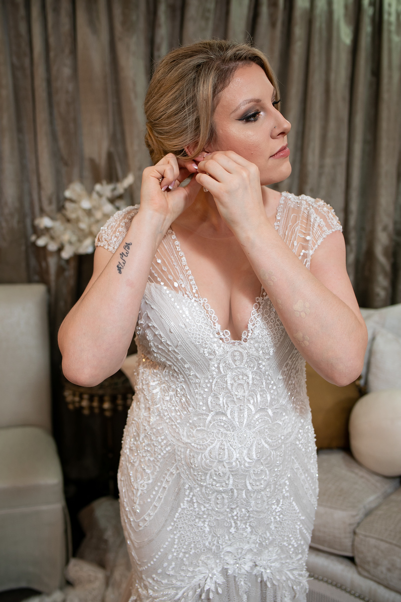 bride in a lace pure white wedding dress putting on pearl earrings before her wedding