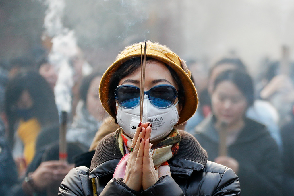 . A Chinese woman wearing a mask and a pair of sunglasses prays while holding burning joss sticks on the first day of the New Year at Yonghegong Lama Temple in Beijing, on a heavily polluted day, Sunday, Jan. 1, 2017. (AP Photo/Andy Wong)