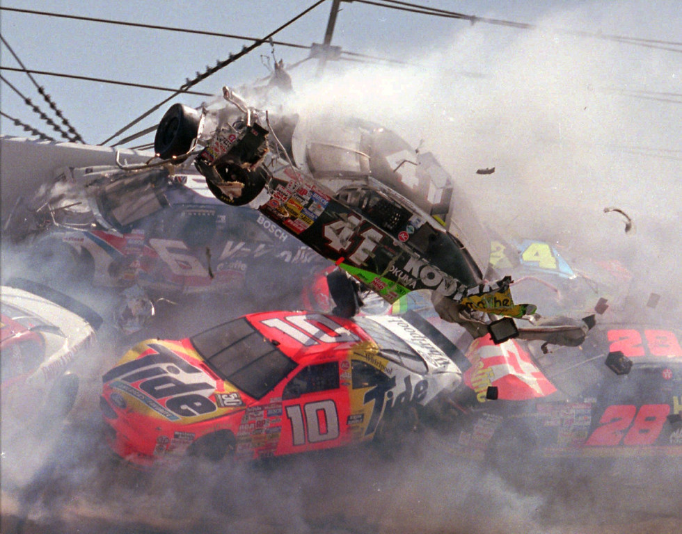 . NASCAR driver Ricky Craven (41) of Newburgh, Maine, flies through the air after tumbling through turn one of the Talladega Superspeedway during the Winston Select 500 Sunday, April 28, 1996.  Driving underneath Craven is Ricky Rudd (10) of Chesapeake, Va.  At right is pole sitter Ernie Irvan (28) of Modesto, Ca.  At least 12 cars were involved in the wreck that caused track officials to red flag the race for nearly an hour to make repairs to the catchfencing. (AP Photo/Ashley Fleming)