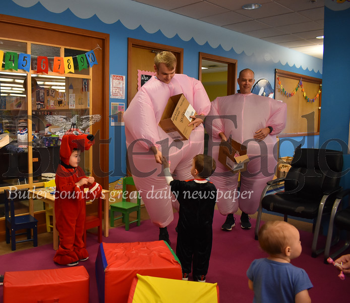 Jordan Grady, project coordinator at Alliance of Nonprofit Resources hands a pink lollipop to Jonah Kramer, 2, of Butler who's dressed as the Cat in the Hat in the children's section of the Butler Public Library at 218 N McKean St, Butler, PA. Clark Rogerson, 3 and a half, of Butler, dressed as Clifford, also received a pink lollipop. Behind Grady is Brian Peffer, IT Director at ANR, who, along with three other ANR employees took to the streets of Butler in inflatable pink costumes to hand out lollipops to the community to raise awareness for breast cancer as October, which is Breast Cancer Awareness Month, comes to a close.
