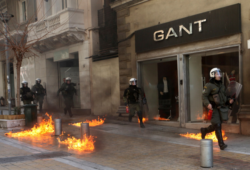 . Riot police run by closed shops after protesters threw a petrol bomb following an anti-austerity march during a 24-hour strike in Athens February 20, 2013. Tens of thousands of Greeks took to the streets of Athens on Wednesday during a nationwide strike against wage cuts and high taxes that kept ferries stuck in ports, schools shut and hospitals with only emergency staff.   REUTERS/Giorgos Moutafis