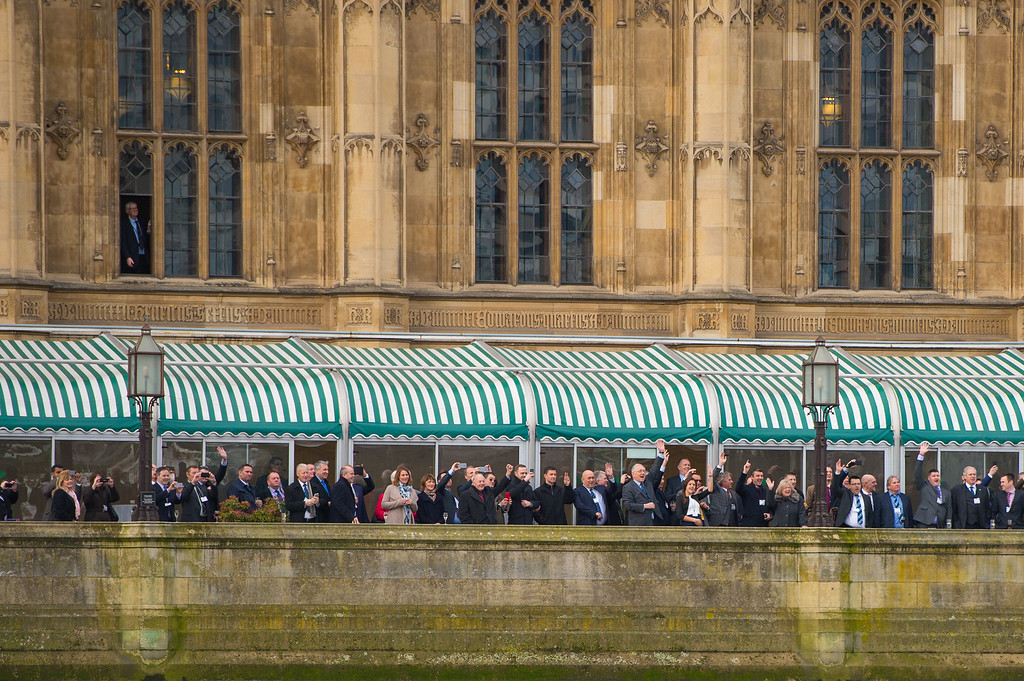. Staff at the Houses of Parliament cheer as the Havengore barge passes as it makes its way along the River Thames during a recreation of the journey it made 50 years ago carrying the coffin of former prime minister Sir Winston Churchill during his state funeral in 1965, from the Tower of London to Westminster on January 30, 2015 in London, England. A series of events are to be held throughout the UK to mark the 50th anniversary of the death Britain\'s war time leader.  (Photo by Dominic Lipinski - WPA Pool/Getty Images)
