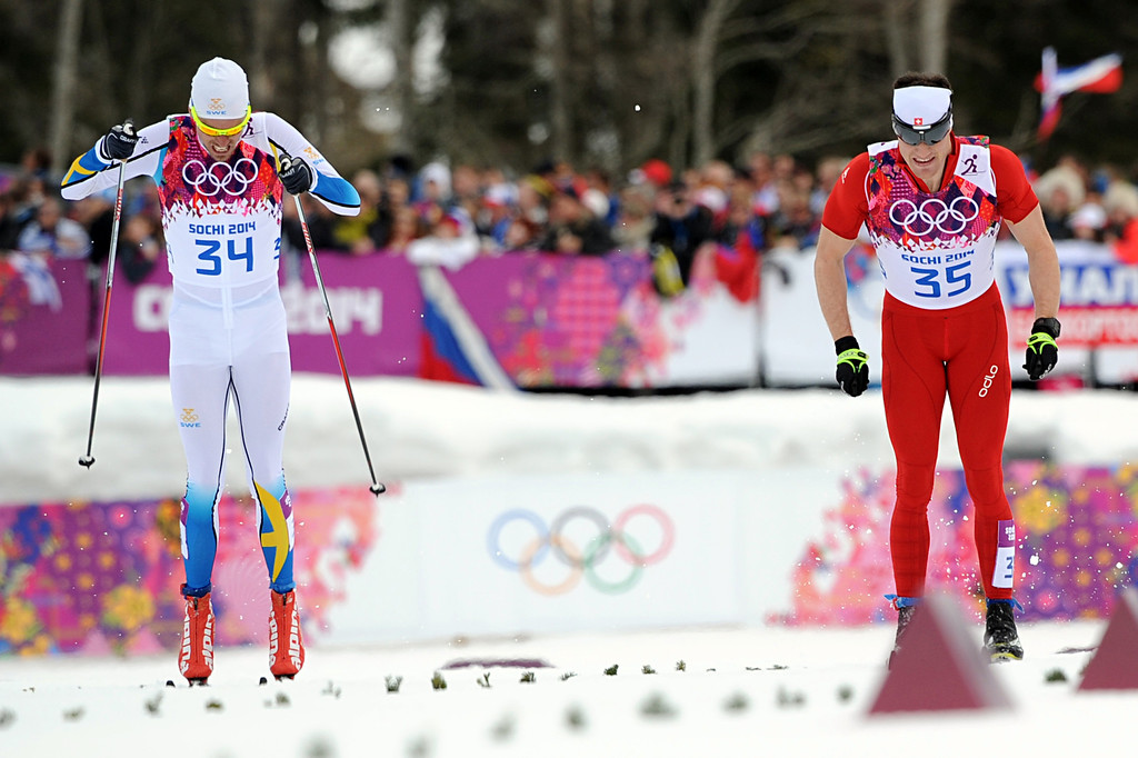 . Silver medalist Sweden\'s Johan Olsson (34) and gold medalist Switzerland\'s Dario Cologna compete in the Men\'s Cross-Country Skiing 15km Classic at the Laura Cross-Country Ski and Biathlon Center during the Sochi Winter Olympics on February 14, 2014 in Rosa Khutor near Sochi. AFP PHOTO / KIRILL  KUDRYAVTSEV/AFP/Getty Images