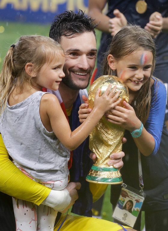 . France goalkeeper Hugo Lloris, center, and children pose with the trophy at the end of the final match between France and Croatia at the 2018 soccer World Cup in the Luzhniki Stadium in Moscow, Russia, Sunday, July 15, 2018. (AP Photo/Matthias Schrader)