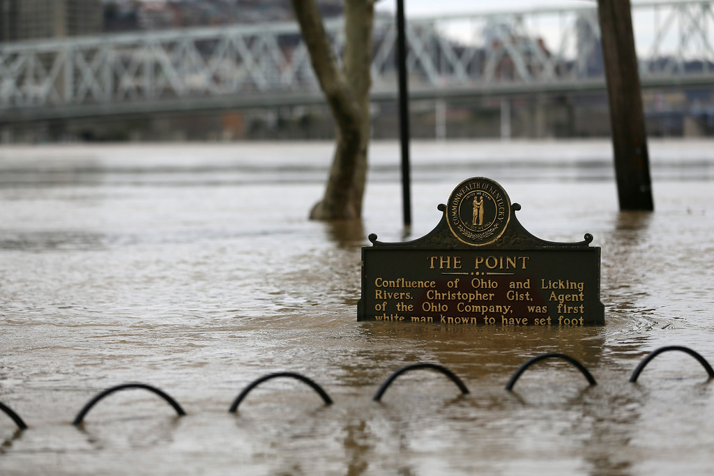 . Flood waters nearly submerge a sign at the confluence of the Ohio and Licking Rivers, in Covington, Ky., Sunday, Feb. 25, 2018. The weather service said moderate flooding was expected along the Ohio River in Kentucky and Ohio, including in Cincinnati, where the river was 8 feet above flood stage Sunday. (Kareem Elgazzar/The Cincinnati Enquirer via AP)
