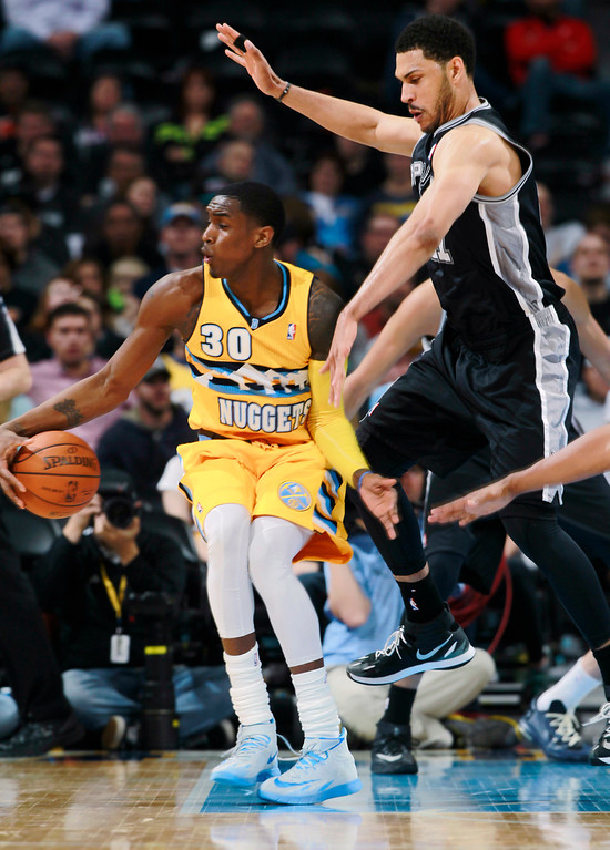 . Denver Nuggets forward Quincy Miller, left, picks up loose ball as San Antonio Spurs forward Jeff Ayers defends in the fourth quarter of the Spurs\' 133-102 victory in an NBA basketball game in Denver on Friday, March 28, 2014. (AP Photo/David Zalubowski)