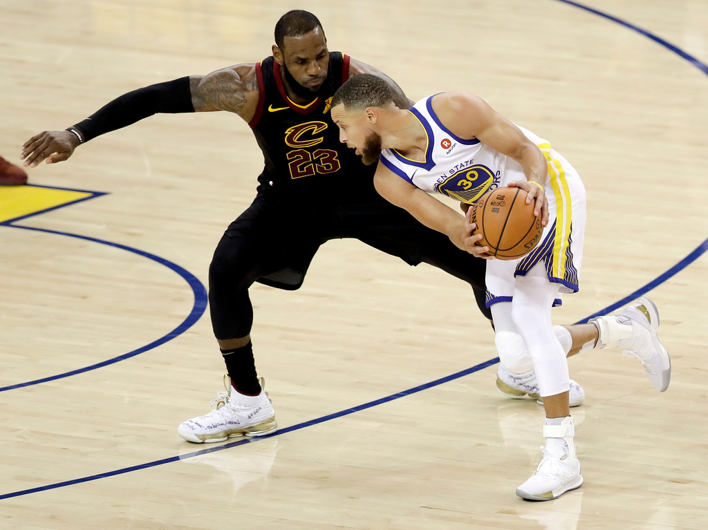 . Cleveland Cavaliers forward LeBron James, left, defends Golden State Warriors guard Stephen Curry during the second half of Game 1 of basketball\'s NBA Finals in Oakland, Calif., Thursday, May 31, 2018. (AP Photo/Marcio Jose Sanchez)