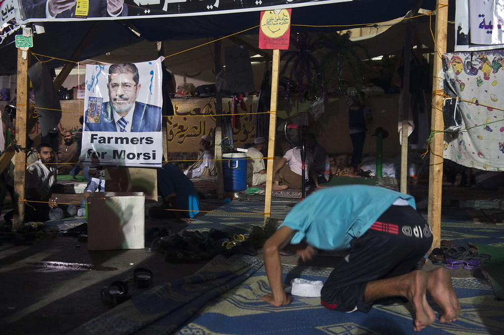 . A member (R) of the Muslim Brotherhood and supporters of Egypt\'s ousted president Mohammed Morsi prays during a sit-in protest outside the Rabaa al-Adawiya mosque in Cairo on August 12, 2013. Egypt\'s judiciary extended ousted president Mohamed Morsi\'s detention as his supporters marched through Cairo in defiance of the expiry of a government ultimatum to dismantle their huge protest camps.   KHALED DESOUKI/AFP/Getty Images