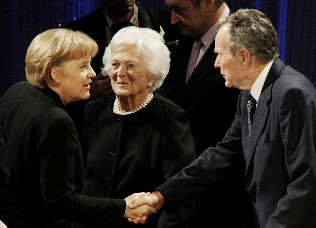 . Former U.S. President George H.W. Bush, right, shakes hands with German Chancellor Angela Merkel, left, as Barbara Bush looks on during an event in Berlin, Germany, Saturday, Oct. 31, 2009, marking the start of celebrations here recalling the crumbling of the Berlin wall on Nov. 9, 1989. (AP Photo/Herbert Knosowski)