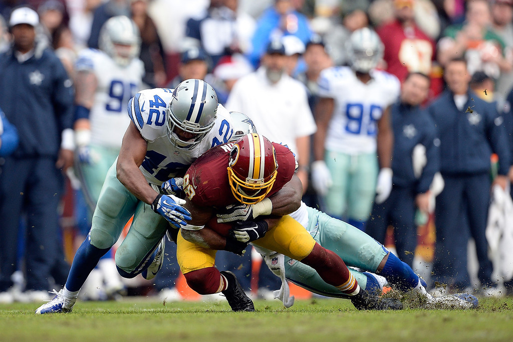 . Pierre Garcon #88 of the Washington Redskins is tackled by Barry Church #42 of the Dallas Cowboys in the second quarter during an NFL game at FedExField on December 22, 2013 in Landover, Maryland.  (Photo by Patrick McDermott/Getty Images)