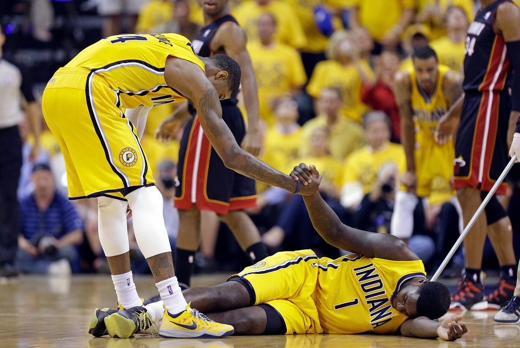 . Indiana Pacers forward Paul George helps guard Lance Stephenson off the floor after Stephenson committed a foul against the Miami Heat during the second half of Game 2 of the NBA basketball Eastern Conference finals in Indianapolis, Tuesday, May 20, 2014. (AP Photo/Michael Conroy)