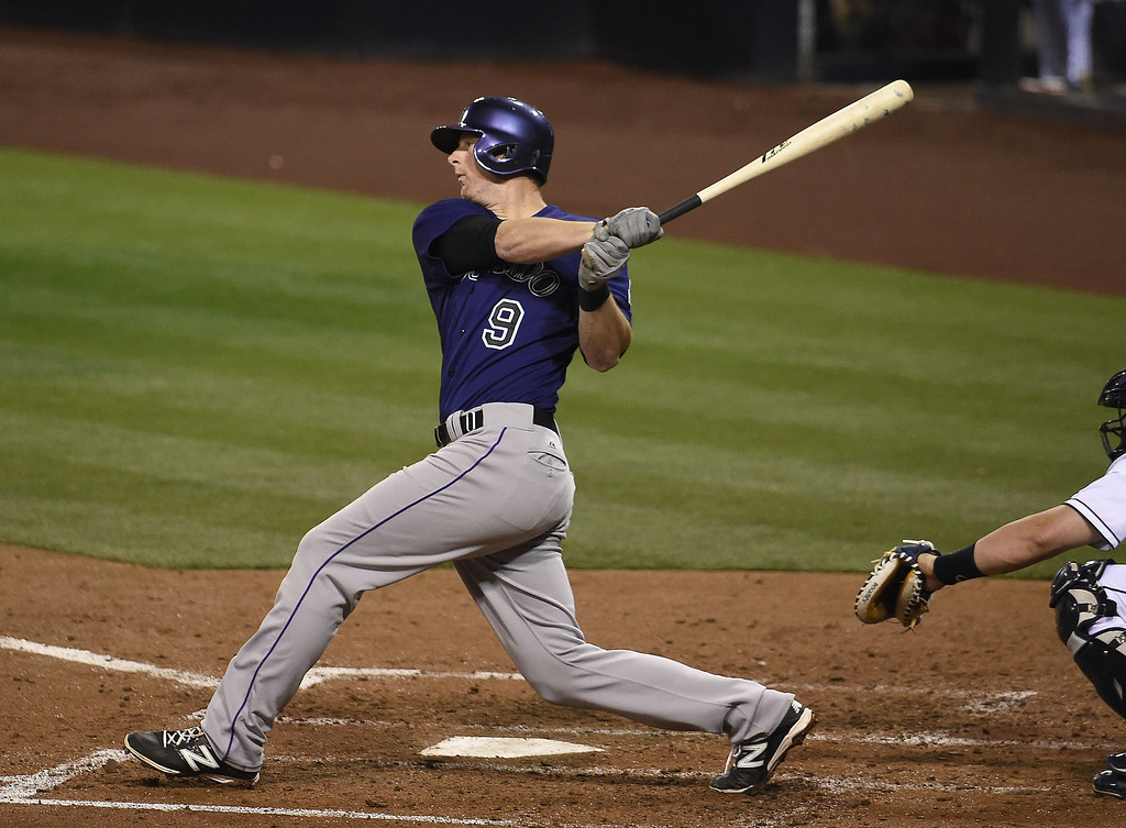 . DJ LeMahieu #9 of the Colorado Rockies hits an RBI single during the fourth inning of a  baseball game against the San Diego Padres at Petco Park April 14, 2014 in San Diego, California.  (Photo by Denis Poroy/Getty Images)