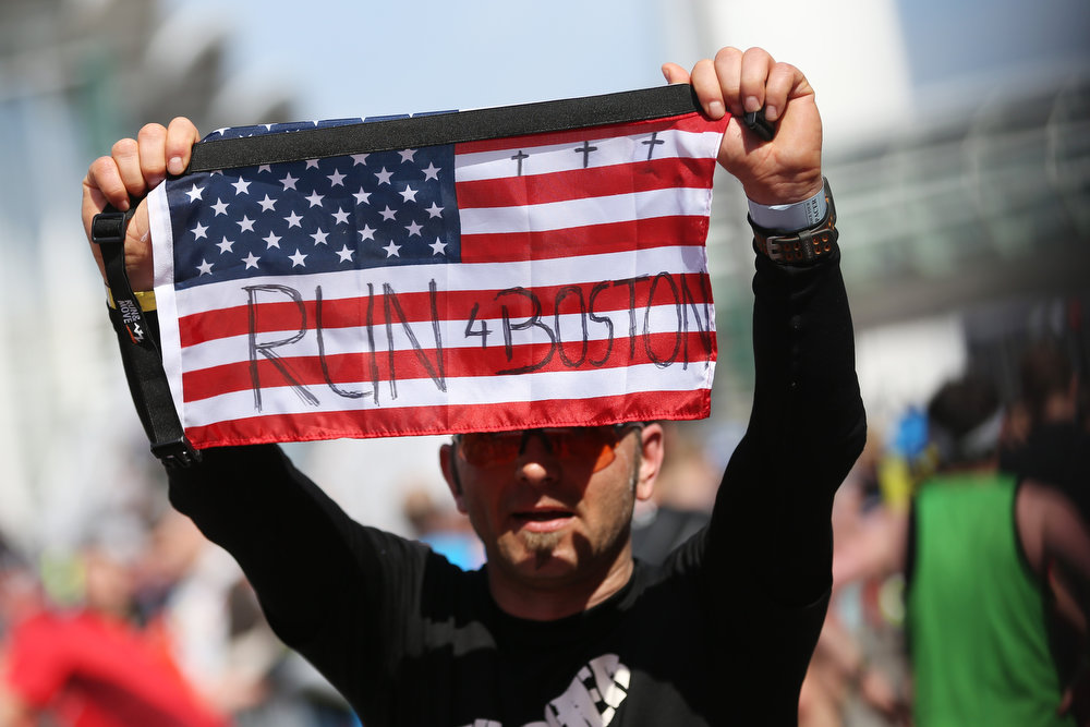 Description of . A runner holds an American flag with the writing 'Run 4 Boston' during the Hamburg, northern Germany, marathon, Sunday, April 21, 2013.  (AP Photo/dpa, Christian Charisius)