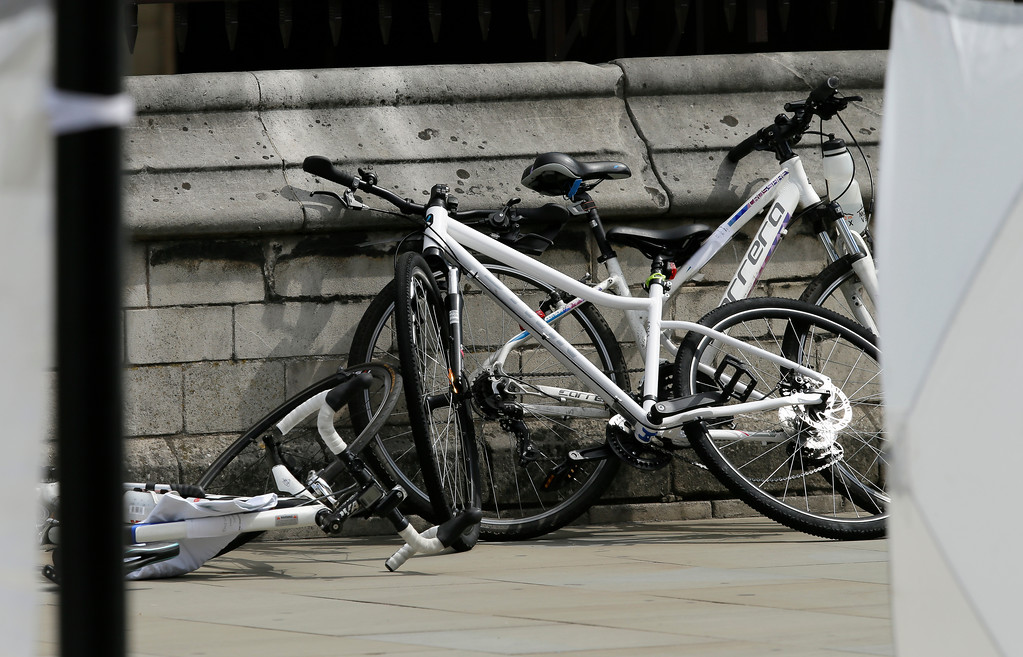 . Bicycles are placed against a wall near the scene where a car crashed into security barriers outside the Houses of Parliament in London, Tuesday, Aug. 14, 2018. Authorities said in a statement Tuesday that a man in his 20s was arrested on suspicion of terrorist offenses after a silver Ford Fiesta collided with a number of cyclists and pedestrians before crashing into the barriers during the morning rush hour. (AP Photo/Tim Ireland)
