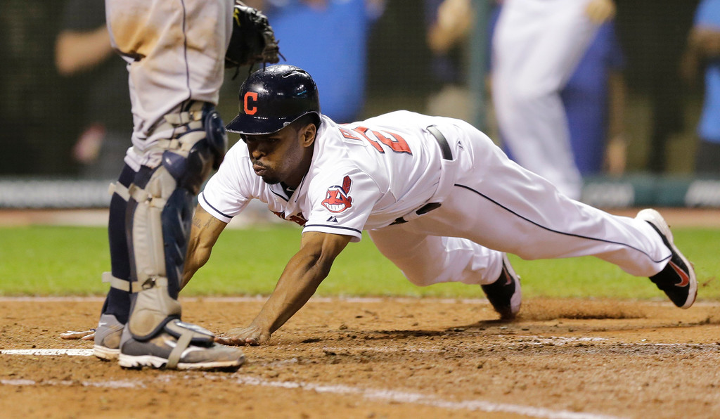 . Cleveland Indians\' Michael Bourn dives into home plate to score on a hit by Michael Brantley in the seventh inning of a baseball game against the Detroit Tigers, Thursday, Sept. 4, 2014, in Cleveland. (AP Photo/Tony Dejak)