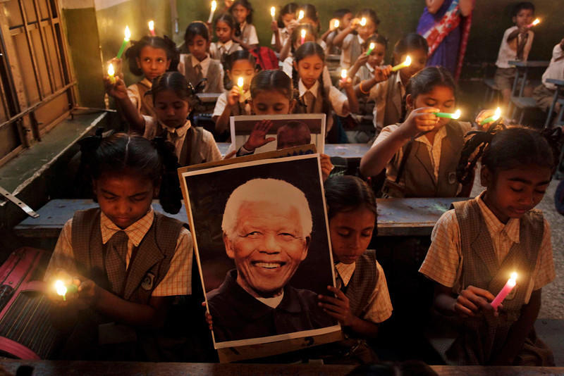 . Young Indian schoolchildren hold candles and portrait of former South African President Nelson Mandela as they pay tribute to him on hearing of his death, at a school in Ahmadabad, India, Friday, Dec. 6, 2013.  Mandela, South Africa\'s first black president, died Thursday in Johannesburg, South Africa after a long illness. He was 95. (AP Photo/Ajit Solanki)